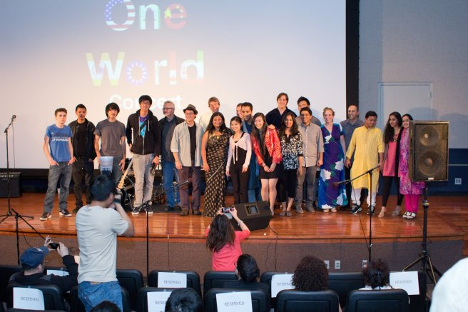"""a group of students in various international clothing on a stage with the words """"One World Concert"""" behind them"""